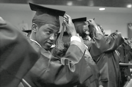 In this May 5, 2014 photo, Krishaun Branch, left, moves the tassel on his mortarboard to the left side after graduating from Fisk University in Nashville, Tenn. (AP Photo/Mark Humphrey)